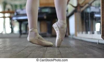 Yound ballet dancer warm-up her legs - Close up yound ballet...