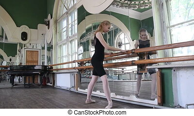 Young ballerina dancing on pointe with her legs and warm-up...