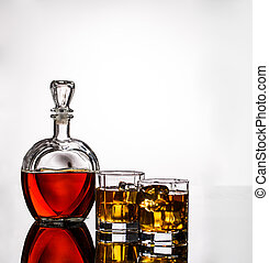 Decanter, two glasses of alcohol and ice on gray background,...