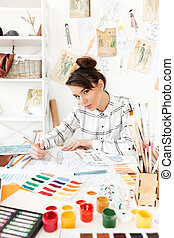 Young serious woman fashion illustrator drawing. - Image of...