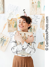 Lovely young woman fahion designer holding her sketchbook -...