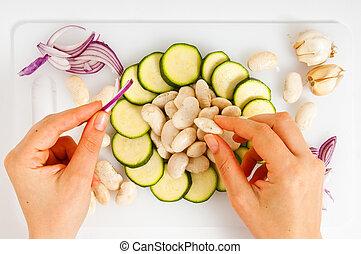 composizione di verdure con mani su tegliere bianco