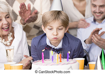 Boy blowing out candles on his birthday cake and his family...