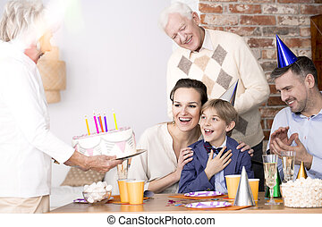 Grandma bringing birthday cake to a party