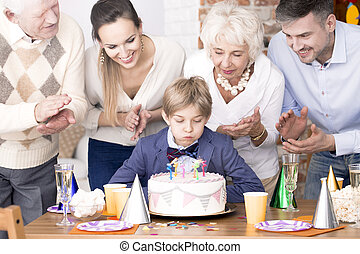Boy blowing out candles on birthday cake - Little boy...