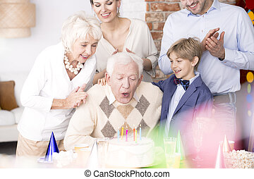 Grandpa blowing out candles on birthday cake - Grandpa...