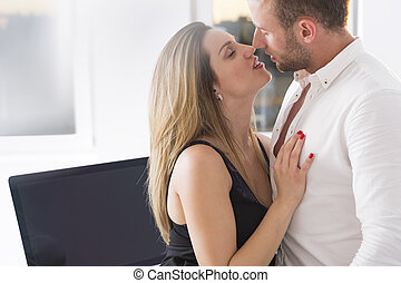 Sensual kiss at work-young business romance couple