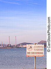 No Swimming sign by the beach, with power plant station in...