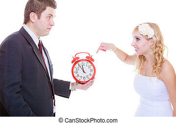 Groom holding big red clock yelling and bride