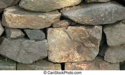 Wall of stacked slabs of stone. Dry wall built without...