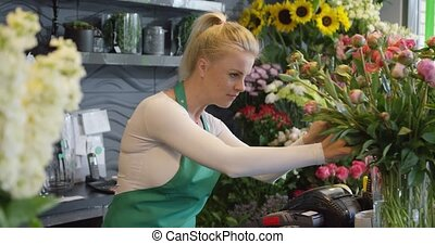 Young woman in floral shop - Side view of female employee in...