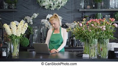 Woman with laptop in floral shop - Young female worker...