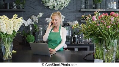 Woman talking phone in floral shop - Female florist standing...