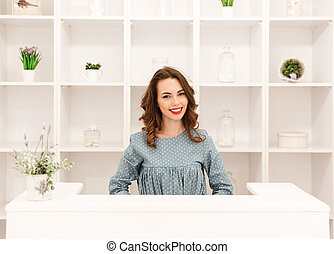 Happy young lady sitting in shop over shelf background -...