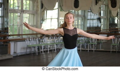Ballerina dance on pointe in the ballet hall