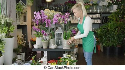 Florist working in shop - Side view of woman in apron...
