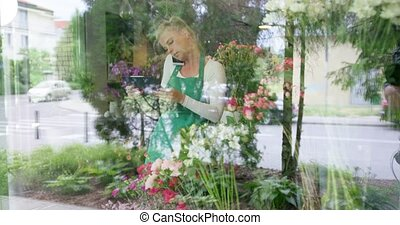 Woman in floral shop talking phone - Shot through glass of...
