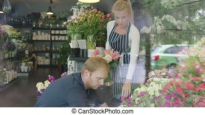 Man and woman in floral shop working - Shot through glass of...
