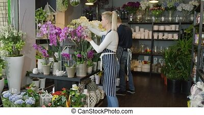 Woman in uniform working in floral shop - Side view of woman...