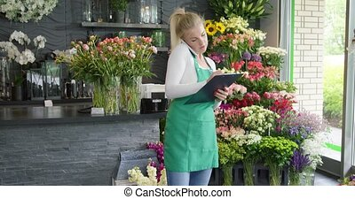 Woman talking phone and taking order - Female florist in...