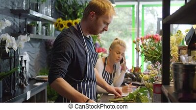 Florists in shop working - Side view of man wearing striped...