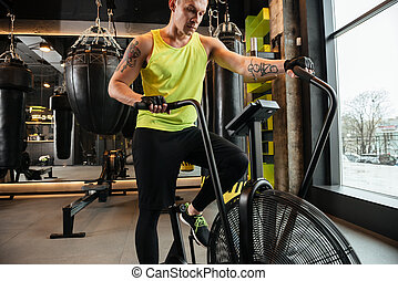 Cropped image of a muscular young sportsman doing cardio...