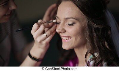 The first half of the day. Wedding preparation. Makeup artist apply makeup to the face and eyes of a joyful bride.