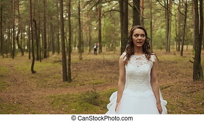 Happy couple in a forest in the fresh air. The groom goes to...