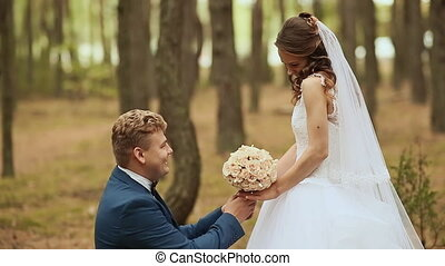 The groom gives the bride a bouquet of her standing on one knee on nature. Happy groom lifts the bride circling her.