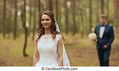 Happy couple in a forest in the fresh air. The groom goes to the bride with a beautiful bouquet. The bride stood still, waiting.