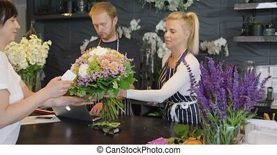 Coworkers and customer in floral shop - Male worker using...