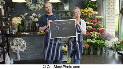Florists posing with tablet - Cheerful coworkers smiling at...