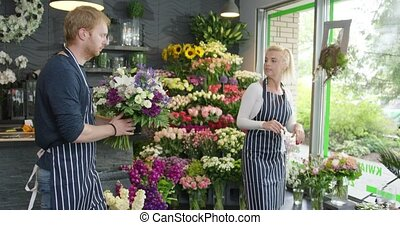 People working in floral shop - Young blonde woman talking...