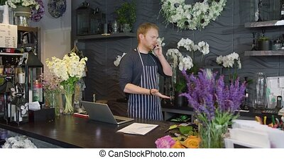 Man talking phone while working in shop - Young man wearing...