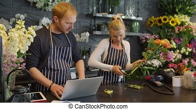Man and woman working together - Young man in striped apron...