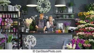 Employees in floral shop - Man in apron browsing laptop...