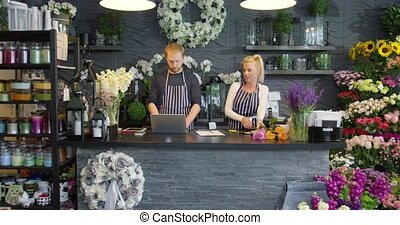 Two people working in shop - Smiling woman in striped apron...