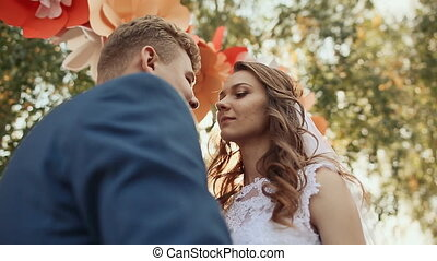 Happy newlywed couple kissing on the romantic wedding aisle with decorations in the form of flowers. It falls a ray of sunshine.