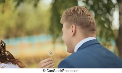 Wedding day. A beautiful and happy couple blowing dandelion on a green meadow.