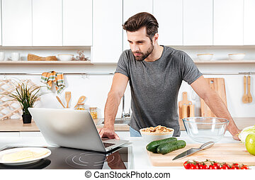 Man looking recipe on laptop in kitchen at home - Man...