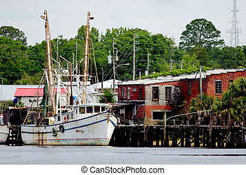 Shrimp boat docked at a wooden pier in North Carolina
