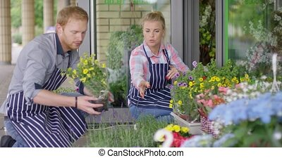 Young florists working outside - Young male and female...