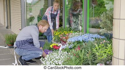 Workers in floral shop - Side view of two young people in...