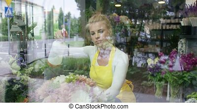 Woman sprinkling flowers in shop - Shot through glass of...