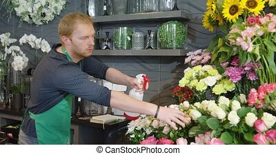 Man refreshing flowers - Side view of man in green apron...