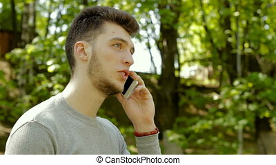 cheerful young gay talking on the phone outdoors and...