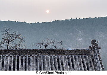 sun over roof of pagoda on East Hill in Longmen - LUOYANG,...