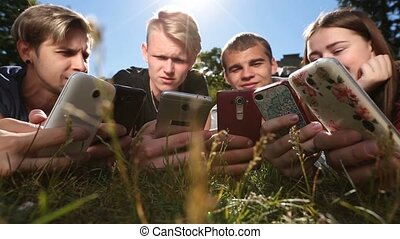 Friends in circle using smartphones on park lawn - Closeup...
