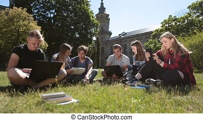 Students studying with laptop and tablet on grass - Group of...