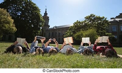 Group of busy students studying together in park - Low view...